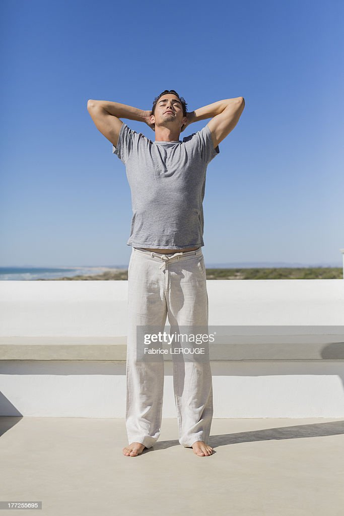 Man standing with hands behind head