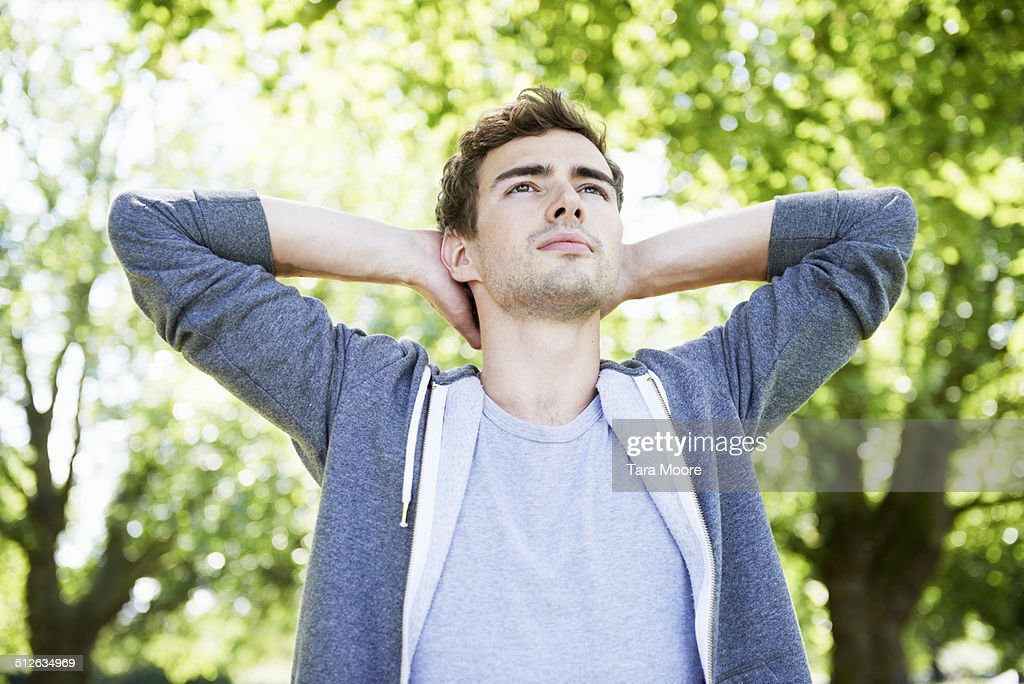 man standing with hands behind head : Stock Photo