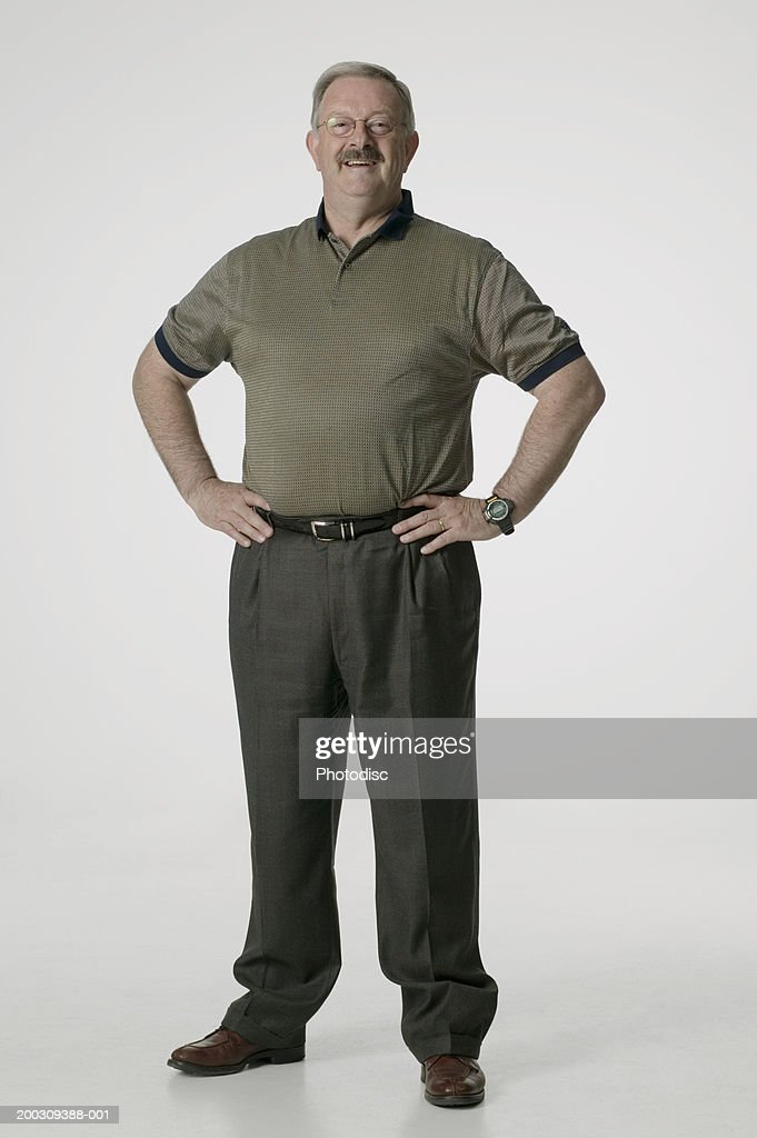Man standing with hands on hips, posing in studio, portrait : Stock Photo