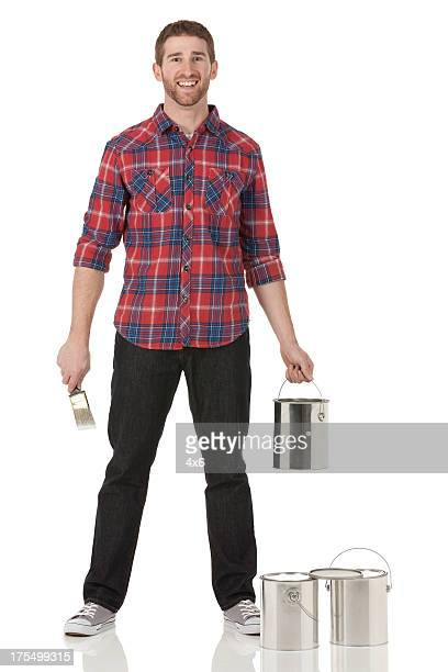 Man standing with paint can and paintbrush