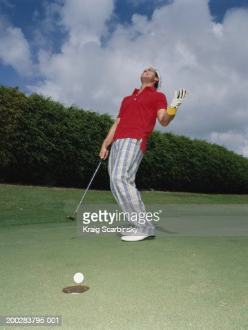 Man standing with raised hand, golf ball at edge of hole in foreground