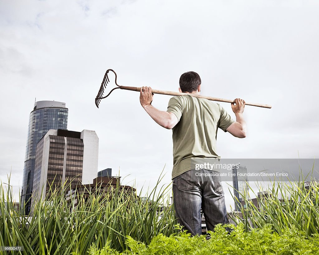 man standing with rake on shoulders