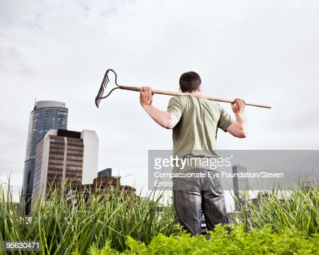 man standing with rake on shoulders