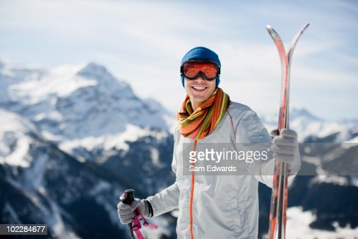 Man standing with skis on mountain top