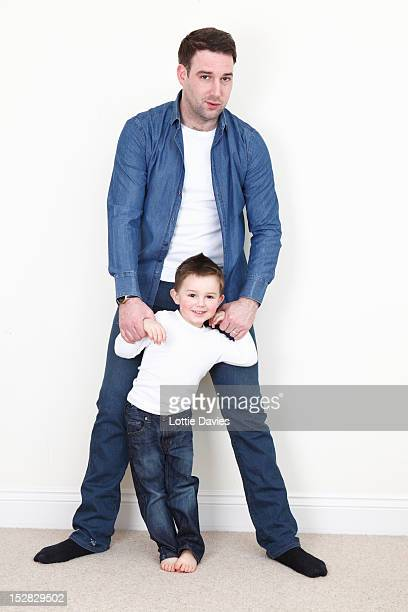Man standing with son indoors