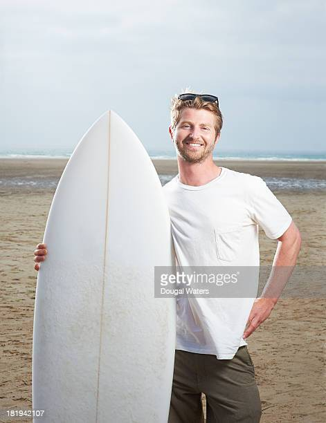 Man standing with surf board at beach.