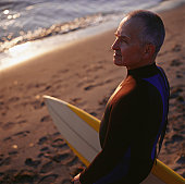Man standing with surfboard at ocean, portrait, elevated view