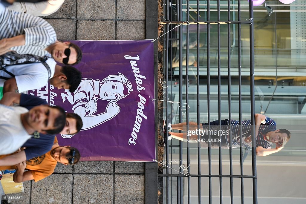 A man stands above a banner of left wing party Podemos reading 'Together We Can' during Spain's general elections in Madrid on June 26, 2016. Spain's ruling conservative Popular Party (PP) took first place in a repeat general election on June 26 but fell well short of a majority while far-left formation Unidos Podemos came second, an exit poll showed. / AFP / GERARD