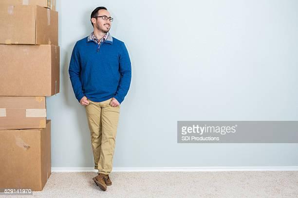 Homme se dresse contre mur vierge avec une pile de boîtes