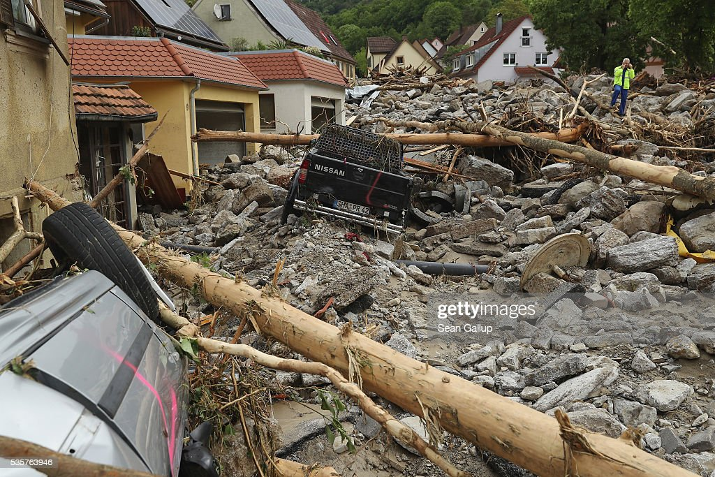 A man stands among boulders, smashed trees and cars and other debris that cover a street in the village center following a furious flash flood the night before on May 30, 2016 in Braunsbach, Germany. The flood tore through Braunsbach, crushing cars, ripping corners of houses and flooding homes during a storm that hit southwestern Germany. Miraculously no one in Braunsbach was killed, though three people died as a result of the storm in other parts of the country.