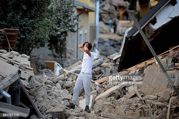 TOPSHOT A man stands among damaged buildings after a strong earthquake hit central Italy in Amatrice on August 24 2016 A powerful 62magnitude...