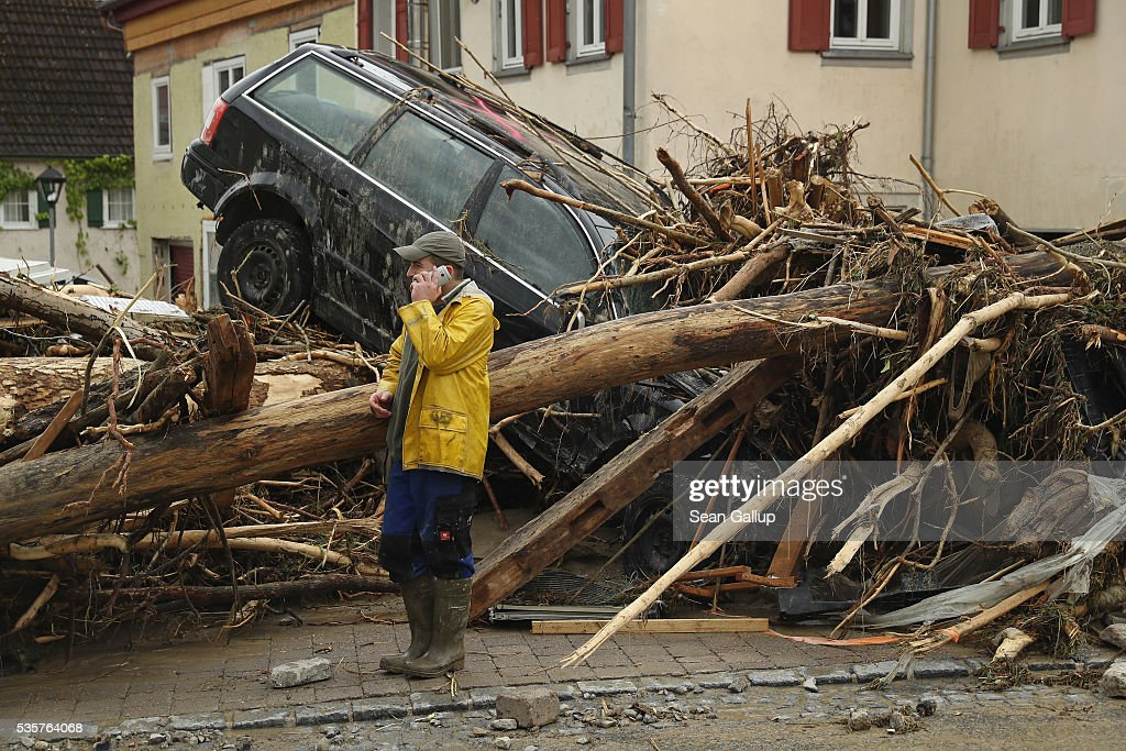 A man stands among smashed trees, cars and other debris that cover a street in the village center following a furious flash flood the night before on May 30, 2016 in Braunsbach, Germany. The flood tore through Braunsbach, crushing cars, ripping corners of houses and flooding homes during a storm that hit southwestern Germany. Miraculously no one in Braunsbach was killed, though three people died as a result of the storm in other parts of the country.