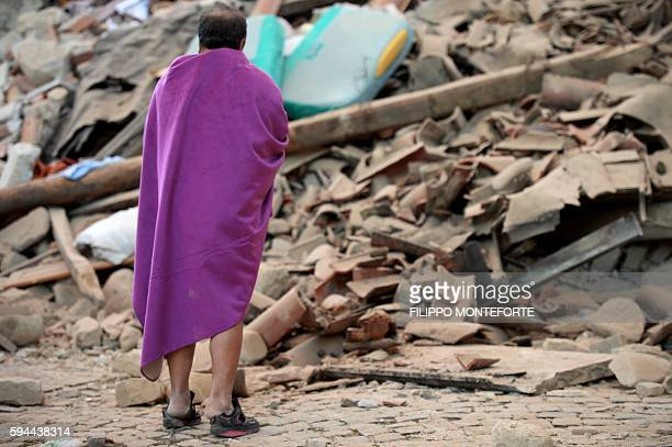 TOPSHOT A man stands among the rubble of a house after a strong earthquake hit Amatrice on August 24 2016 Central Italy was struck by a powerful...