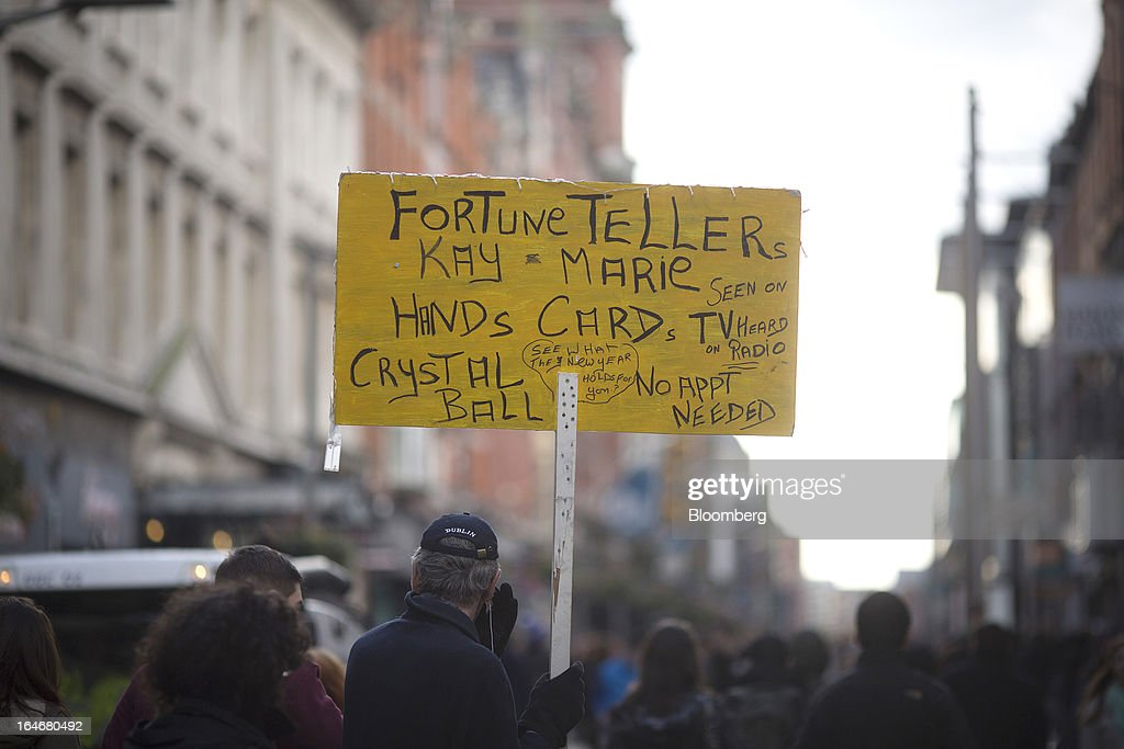 A man stands and holds a board advertising the services of a fortune teller, named Kay Marie, as pedestrians walk past on Henry Street in Dublin, Ireland, on Saturday, March 16, 2013. Ireland's renewed competiveness makes it a beacon for the U.S. companies such as EBay, Google Inc. and Facebook Inc., which have expanded their operations in the country over the past two years. Photographer: Simon Dawson/Bloomberg via Getty Images