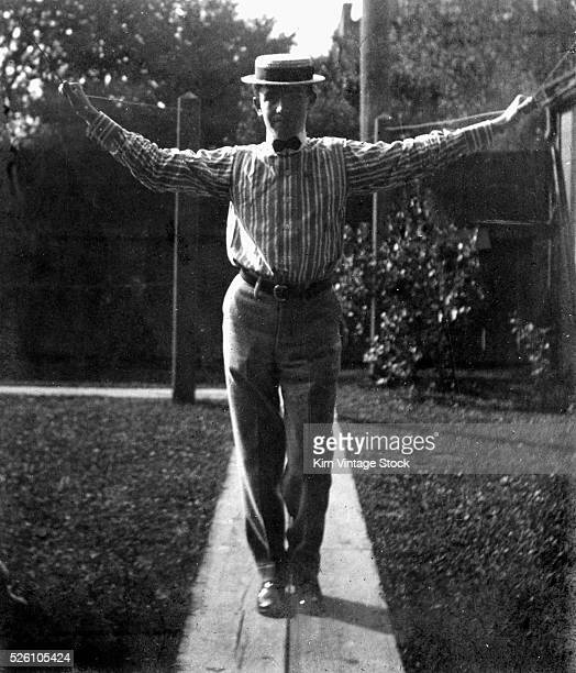 A man stands and holds the clothes line in the backyard ca 1910