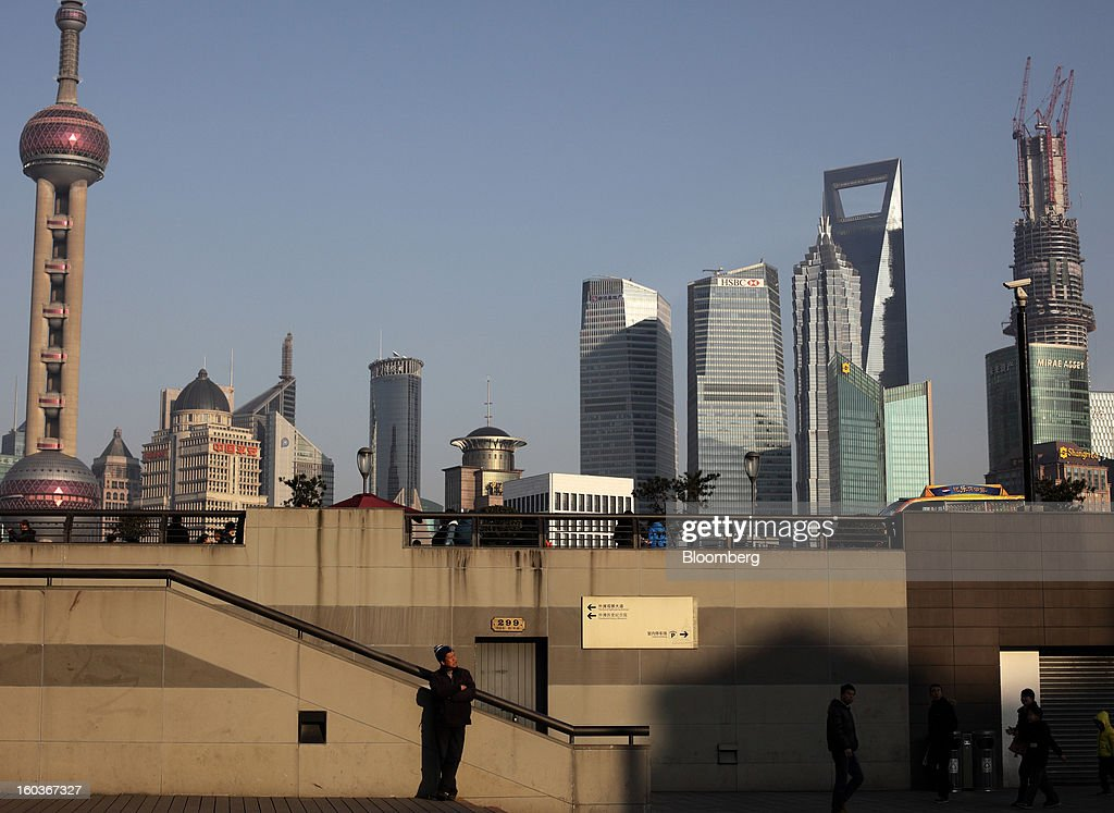 A man stands and people walk on the bund as commercial buildings stand in the Pudong area in Shanghai, China, on Monday, Jan. 28, 2013. China's economic growth accelerated for the first time in two years as government efforts to revive demand drove a rebound in industrial output, retail sales and the housing market. Photographer: Tomohiro Ohsumi/Bloomberg via Getty Images