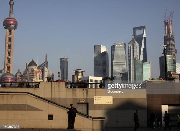 A man stands and people walk on the bund as commercial buildings stand in the Pudong area in Shanghai China on Monday Jan 28 2013 China's economic...