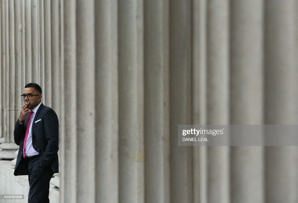 A man stands and smokes a cigarette outsie the Bank of England in central London on June 27, 2016. Britain should only trigger Article 50 to leave the EU when it has a 'clear view' of how its future in the bloc looks, finance minister George Osborne said Monday following last week's shock referendum. London stocks extended their losses in early afternoon Monday, led by banking, airline and property shares, following Britain's vote to leave the EU. / AFP / Daniel Leal-Olivas