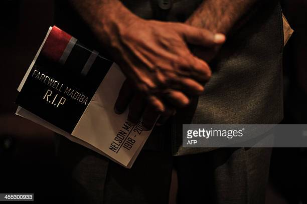 A man stands as he holds a condolence pamphlet of the late former South African president Nelson Mandela during 'Nelson Mandela Remembered' event in...