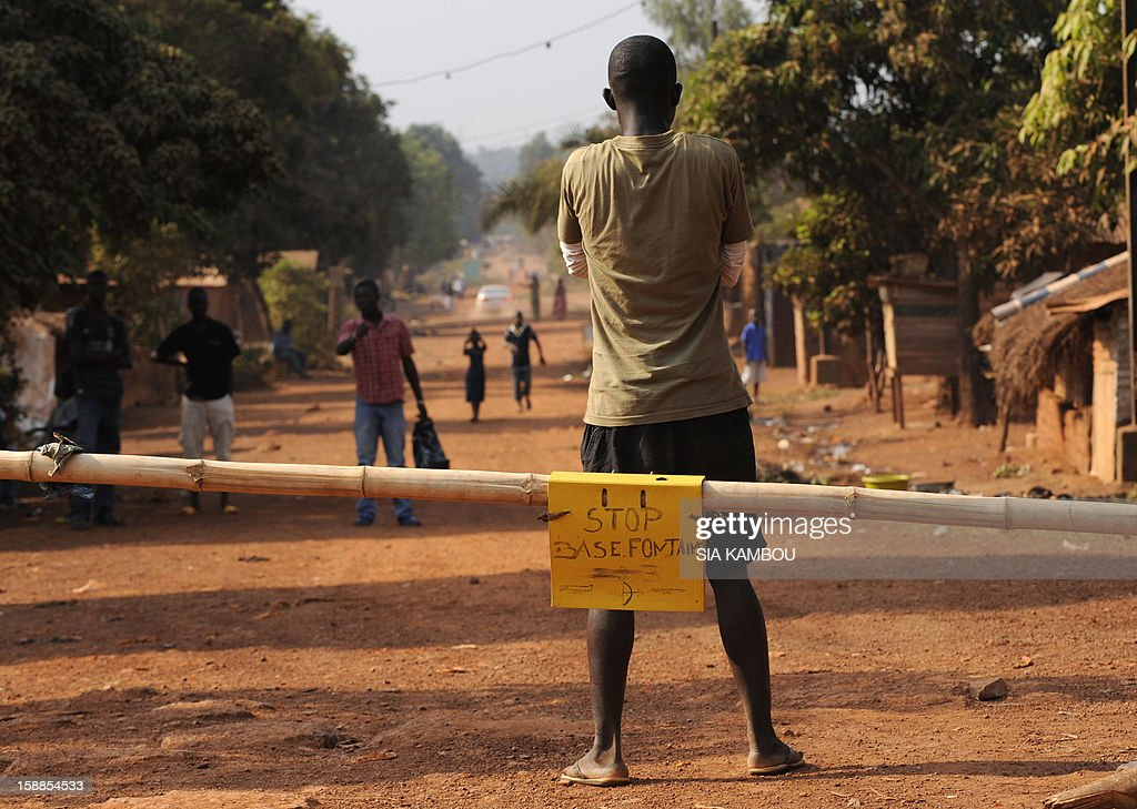 A man stands as members of the ''Centrafrican Young Patriots'' blocked a road to prevent rebels from entering Bangui, on January 1, 2013. The death of a young Muslim man arrested for alleged links to rebels in the Central African Republic sparked clashes on January 1, 2013 in the capital that killed a policeman, a police source said. The unrest erupted as countries in the region sent reinforcements to protect the capital Bangui from rebels who control much of the country and are demanding the departure of President Francois Bozize.