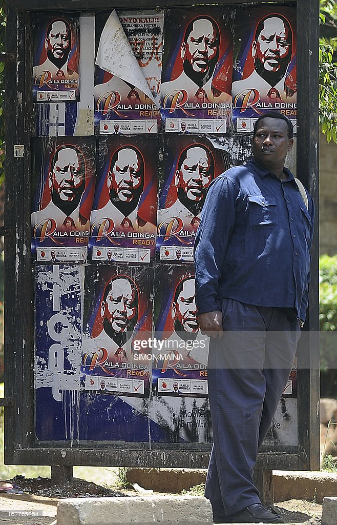 A man stands at a bus stop covered with posters advertising Presidential candidate and Prime Minister Raila Odinga on February 26, 2013 in the sprawling Kibera slums. Kenya is gearing up for presidential, gubernatorial, senatorial elections on March 4, the first since bloody post-poll violence five years ago in which more than 1,100 people died after contested results.
