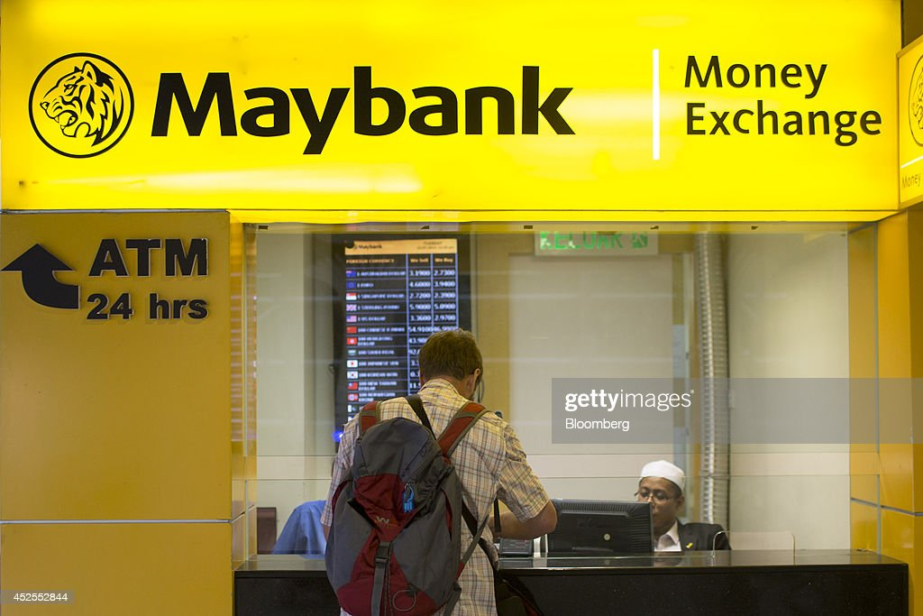 A man stands at a Malayan Banking Bhd. (Maybank) currency exchange kiosk in at Kuala Lumpur International Airport (KLIA) in Sepang, Malaysia, on Tuesday, July 22, 2014. Maybank is Malaysia's biggest lender. Photographer: Brent Lewin/Bloomberg via Getty Images