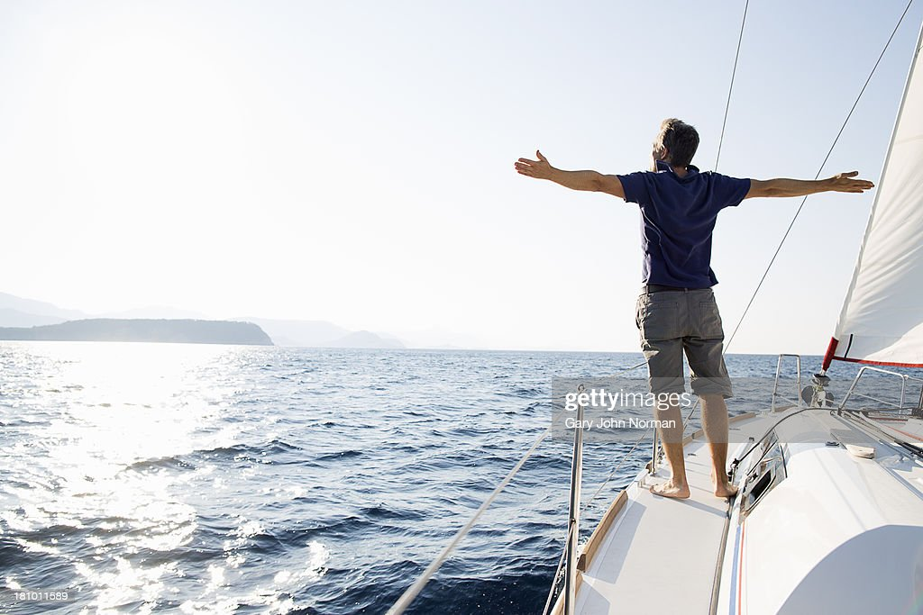 man stands at bow of yacht with arms outstretched : Stockfoto