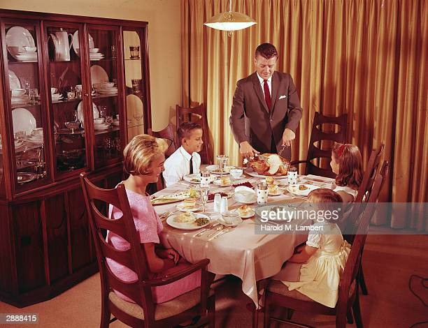 A man stands at the dinner table carving a turkey as his family sits happily at the table circa 1966