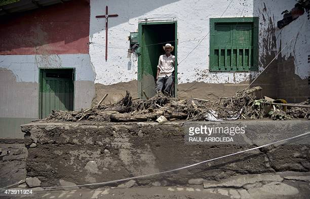A man stands at the door of his house after a landslide in Salgar municipality Antioquia department Colombia on May 18 2015 A massive landslide tore...