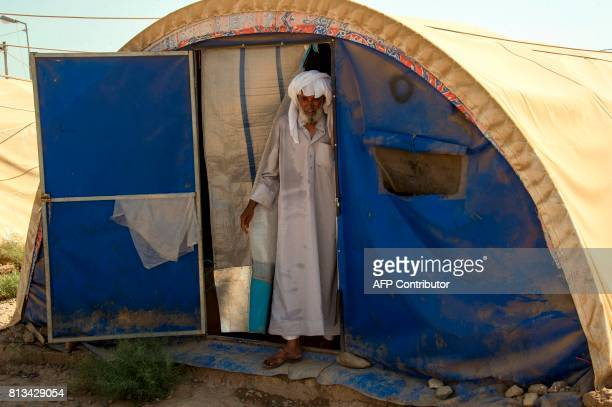 A man stands at the entrance of a tent at a UNHCR refugee camp in Hammam alAlil on the outskirts of Mosul on July 12 2017 Iraqi Prime Minister Haidar...