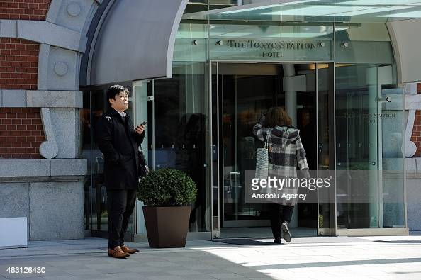 A man stands at the entrance of the Tokyo Station Hotel in the financial and business of Marunouchi district in Tokyo Japan on February 10 2015...