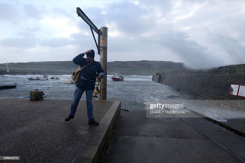 A man stands at the harbour in Auderville, northwestern France, on February 8, 2016, as strong winds hit the region. Winds of over 130 kh/h were recorded in the region where 16 departments have been placed under alert for wind and flooding waves. / AFP / CHARLY TRIBALLEAU