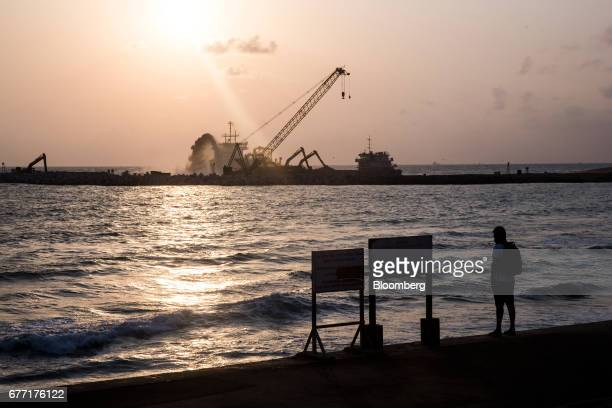 A man stands at the sea front of Galle Face Green as the construction site of the Colombo Port City development stands in the background in Colombo...