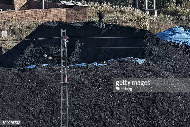 A man stands atop a pile of coal at the Qinhuangdao Port in Qinhuangdao China on Friday Oct 28 2016 China's efforts to quell surging coal prices...