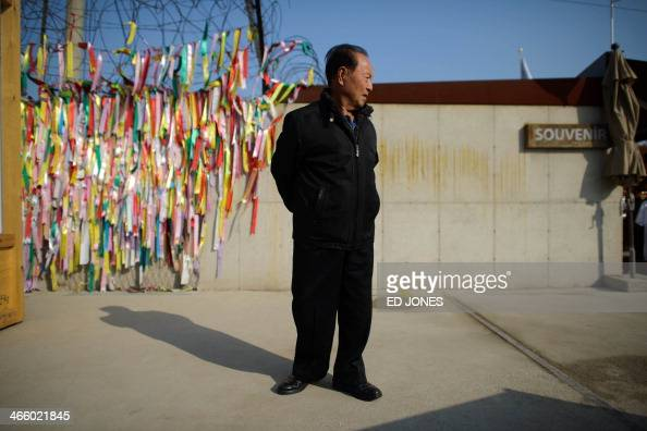 A man stands before messages left on a fence at the Demilitarized Zone at Imjingak Paju in South Korea's Gyeonggi Province on January 31 2014 Many...