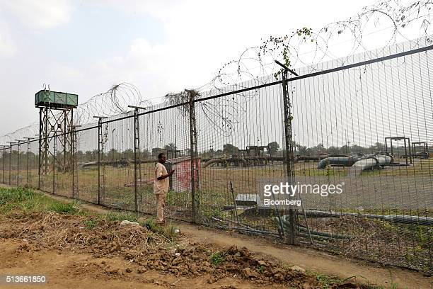 A man stands beside broken security fencing at the Bumo oil manifold site operated by Royal Dutch Shell Plc in KDare Nigeria on Wednesday Jan 13 2016...