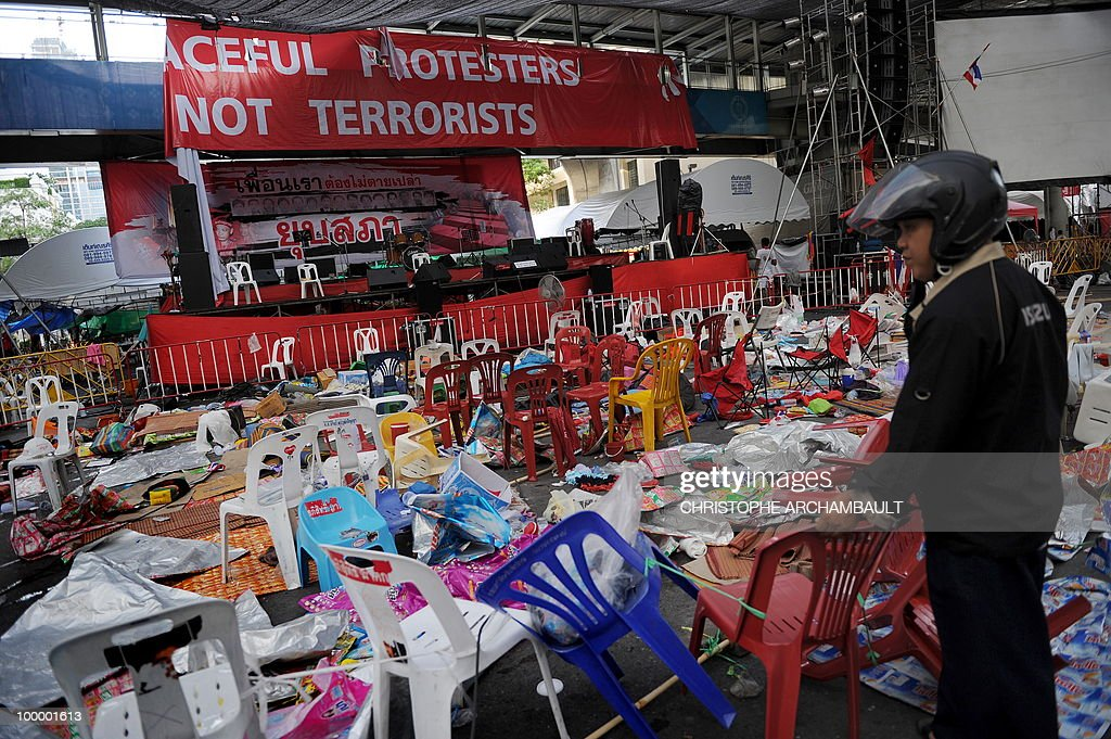 A man stands beside the main stage of a dismantled anti-government protest zone in downtown Bangkok on May 20, 2010. Plumes of smoke hung overhead and gunfire crackled as Bangkok emerged from an curfew aimed at quelling mayhem unleashed by enraged anti-government protesters targeted in an army offensive. AFP PHOTO/Christophe ARCHAMBAULT