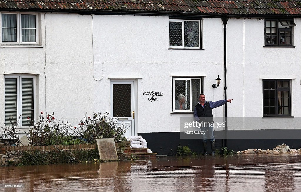 A man stands besides his flooded property in the centre of the village of Ruishton, near Taunton, on November 25, 2012 in Somerset, England. Another band of heavy rain and wind continued to bring disruption to many parts of the country today particularly in the south west which was already suffering from flooding earlier in the week.