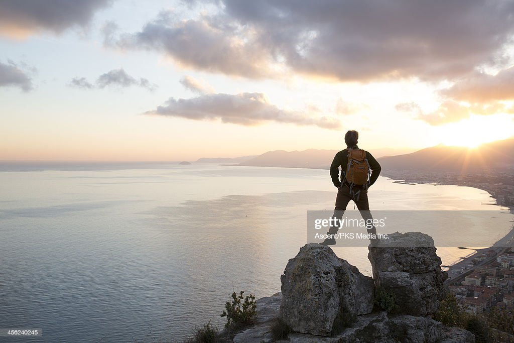 Man stands between rocks above sea, hills and town
