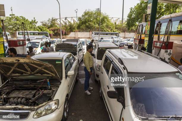 A man stands between vehicles being refueled with compressed natural gas at an Indraprastha Gas Ltd gas station in New Delhi India on Wednesday May...
