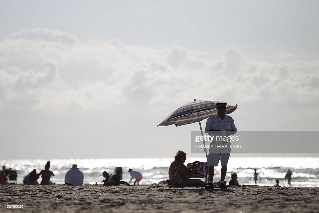 A man stands by a beach umbrella as others sit on the beach on August 18, 2014 in Deauville.