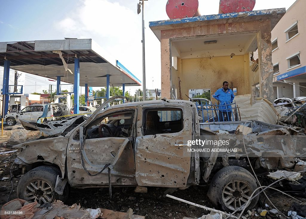 A man stands by a car wreckage in Mogadishu on June 26, 2016 on the scene of the terror attack on a hotel in the Somali capital Mogadishu that killed at least 11 people the day before and was swiftly claimed by Al-Qaeda-affiliated al-Shabab militants. The assault, the latest in a series by the Islamist group targeting hotels and restaurants, began when a suicide bomber detonated a car laden with explosives outside the building. Gunmen then stormed the Naasa Hablood hotel and gunfire rang out for several hours, witnesses said, before the authorities declared the attack over. / AFP / MOHAMED
