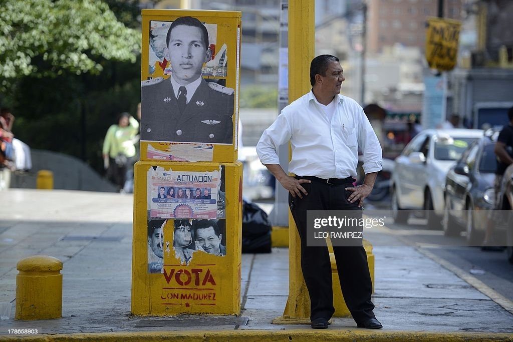 A man stands by a photograph of late Venezuelan former President Hugo Chavez in Caracas on August 23, 2013. Nearly six month of his death, the image of Chavez still appears in buildings and corners of the country. AFP PHOTO/Leo RAMIREZ