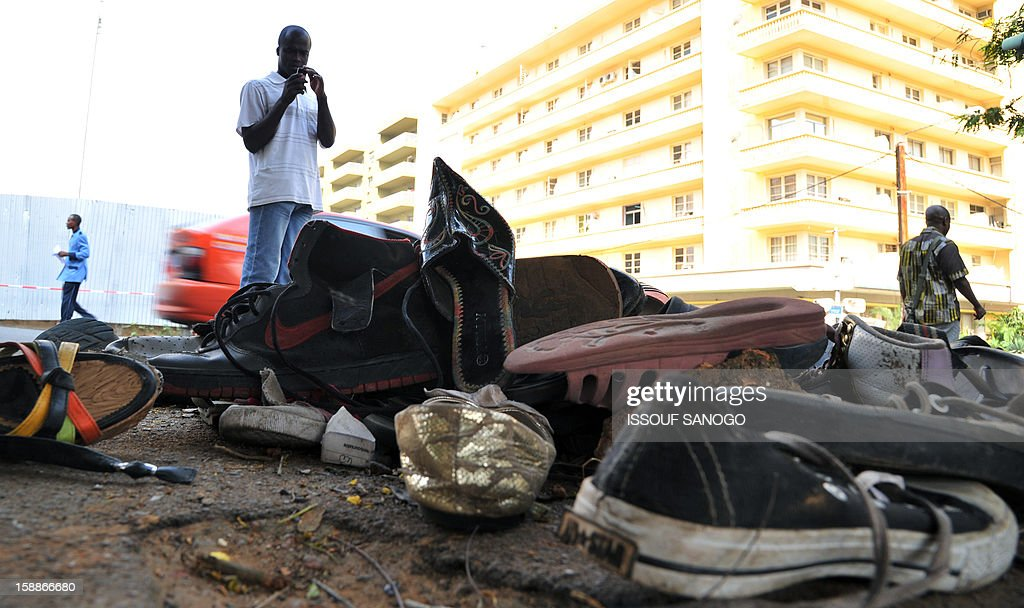 A man stands by a pile of abandoned shoes on January 2, 2013 in the street of Abidjian where at least 60 persons died in a stampede among crowds gathered for celebratory New Year's Eve fireworks that also left dozens injured. Ivory Coast began today three days of national mourning. AFP PHOTO / ISSOUF SANOGO