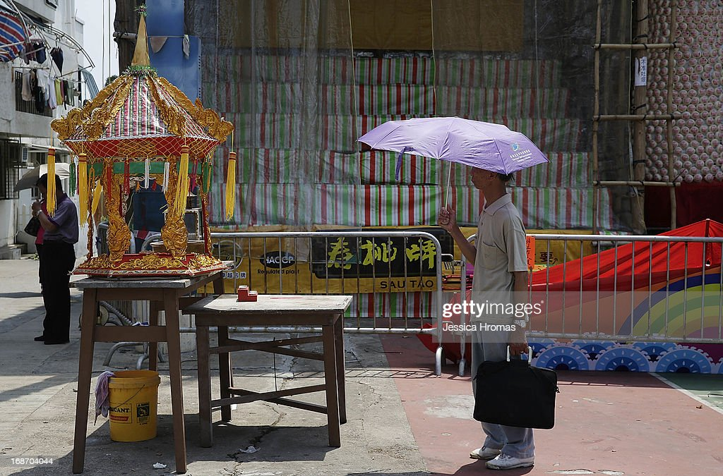 A man stands by a shrine on Cheung Chau Island, on the first day of the Cheung Chau Bun Festival on May 14, 2013 in Hong Kong, Hong Kong. Today is the start of the Cheung Chau Bun Festival which will run until 17 May and celebrates the eight day of the fourth moon in the Chinese calendar.