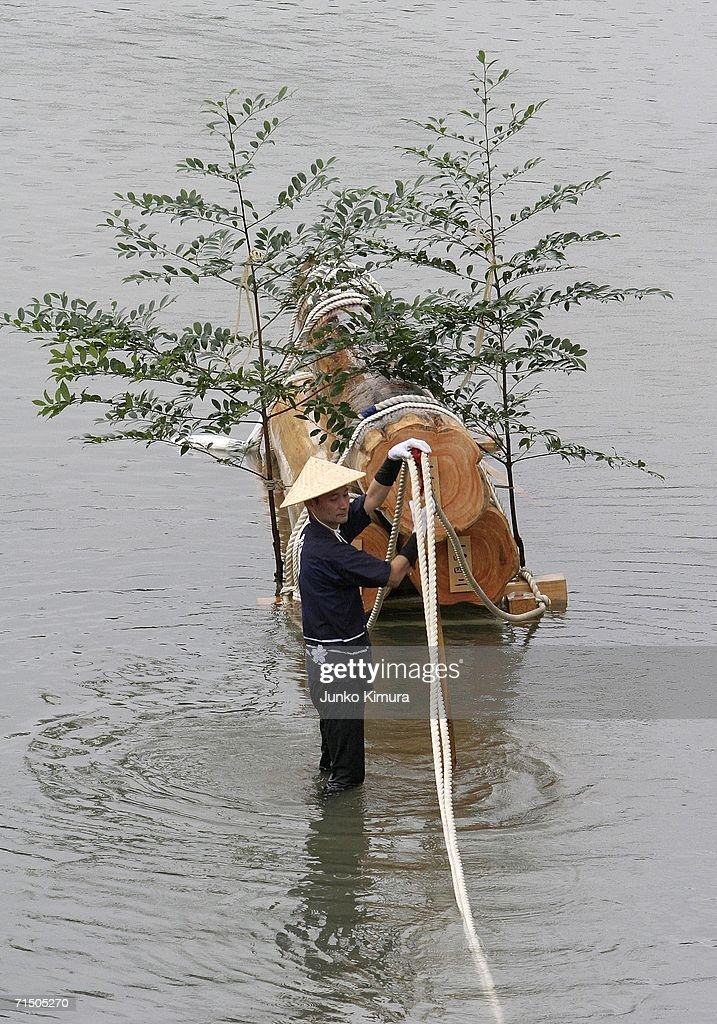 A man stands by the wood being pulled along the Isuzu River to the Inner Shrine of Japan's biggest shrine ?Ise Jingu? during the 62nd Okihiki-Gyoji ceremony on July 23, 2006 in Ise, Mie Prefecture, Japan. The Okihiki-Gyoji ceremony is conducted every 20 years for the last 1300 years and involves the shrines of Ise Jingu being moved and reconstructed and is called the Sengu, it is believed that by performing the Sengu the Japanese people will have their blessings renewed.