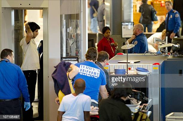 A man stands in a body scanner as others place their luggage through the security screener at Baltimore Washington International airport November 24...