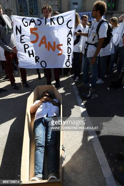 A man stands in a coffin as other hold a banner reading 'Gastro nephro cardio 5 years' during a demonstration on April 18 2017 in front of the...
