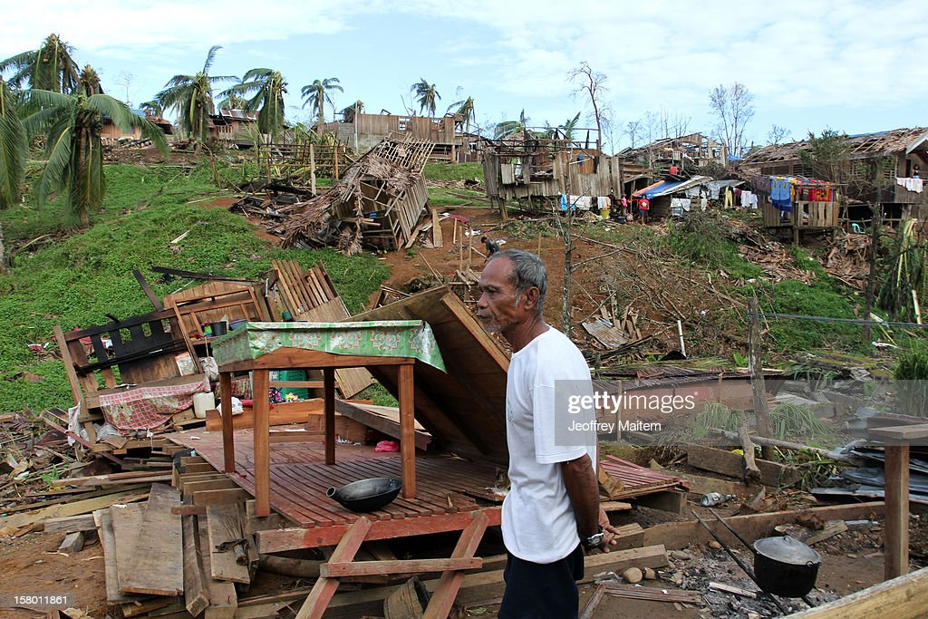 A man stands in a heavily damaged village after Typhoon Bopha, on December 8, 2012 in the town of Boston, Davao Oriental province, Philippines. More than 500 people have been killed and scores of others remain missing after Typhoon Bopha, the strongest storm to hit the Philippines this year, pounded the region. The United Nations Office for the Coordination of Humanitarian Affairs reported that about 5.3 million people are affected and 533 are missing.
