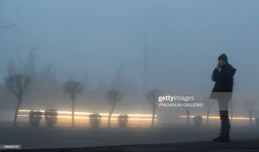 A man stands in a street partially obscured by mist in the Kyrgyzstan's capital Bishkek on January 29, 2013. Mist covered today the Kyrgyz capital while the temperatures reached 1 C (34 F).